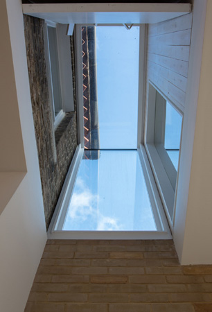 View of the glazed lightwell connecting the existing house and the new extension .